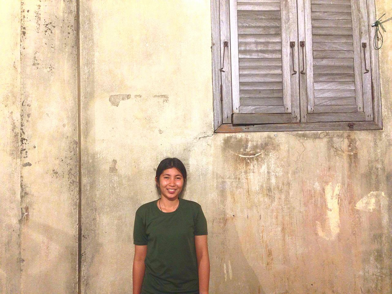 front view, looking at camera, wall - building feature, portrait, architecture, building exterior, real people, built structure, smiling, casual clothing, young adult, one person, house, door, happiness, standing, lifestyles, leisure activity, day, young women, outdoors, corrugated iron, people