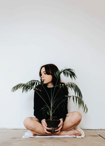 Young woman holding potted plant while sitting on floor against wall