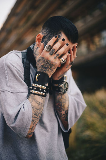 Head over tats One Person Front View Focus On Foreground Real People Tattoo Human Hand Lifestyles Leisure Activity Portrait Hand Casual Clothing Young Adult Young Men Men Waist Up Standing Looking At Camera Human Body Part Obscured Face Photojournalism