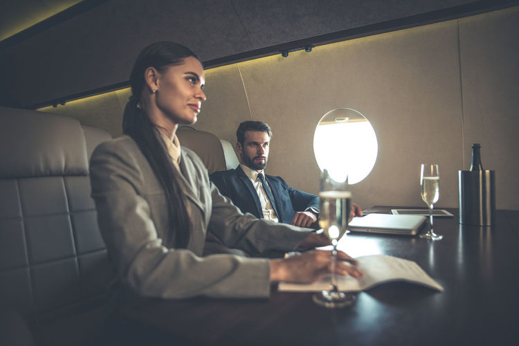Business people sitting at table in airplane