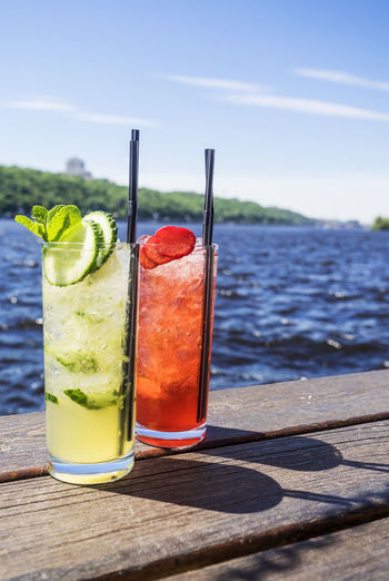 Close-up of cocktail in glasses on jetty against lake
