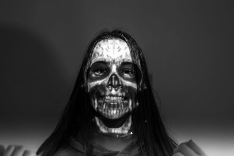 Close-up of spooky woman against black background