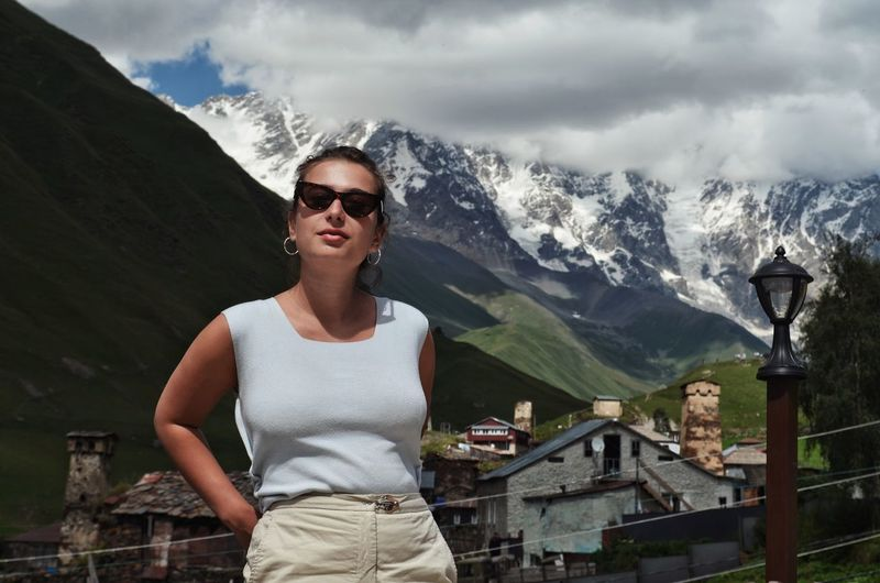 Young woman wearing sunglasses standing on mountain against sky