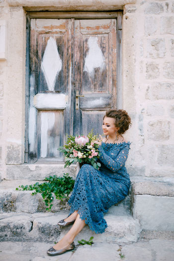 Full length of bride holding flower bouquet sitting by door