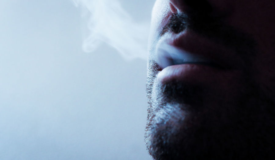 Close-up of man exhaling smoke