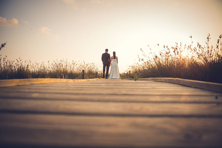 Photograph in the wedding report of a couple. Love Wedding Wedding Photography Adult Bonding Couple - Relationship Day Father Full Length Leisure Activity Lifestyles Love Men Nature Only Men Outdoors People Real People Rear View Selective Focus Sky Sunset Togetherness Two People Women