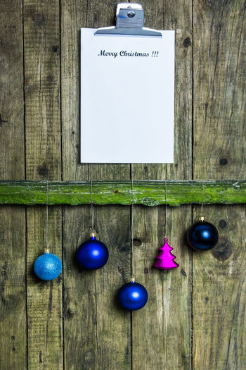 Christmas Ornaments With Clipboard Hanging On Wooden Fence