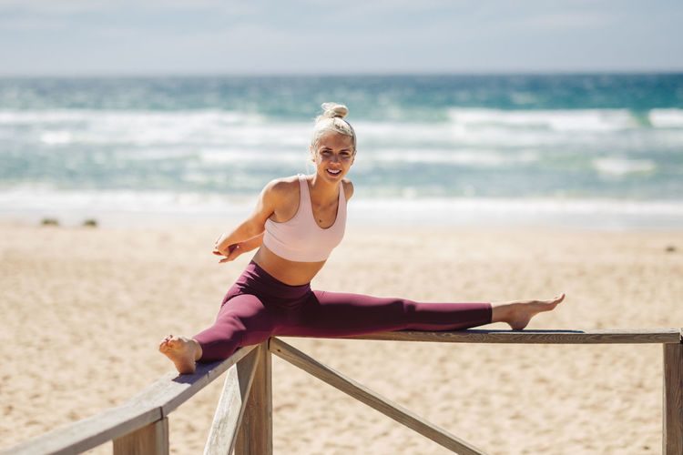 Caucasian woman practicing yoga at seashore. Young female stretching legs in the beach in Cadiz, Andalusia, Spain. One Person Land Beach Sea Full Length Women Leisure Activity Lifestyles Smiling Water Day Exercising Nature Young Adult Sport Real People Young Women Beautiful Woman