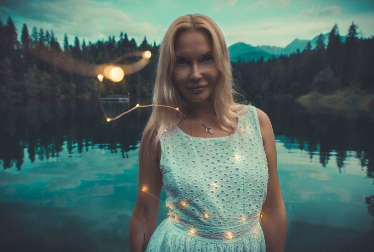 Portrait of woman standing by lake with illuminated lighting equipment