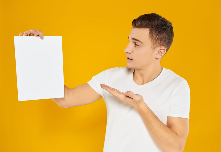 Low angle view of man looking away against yellow background