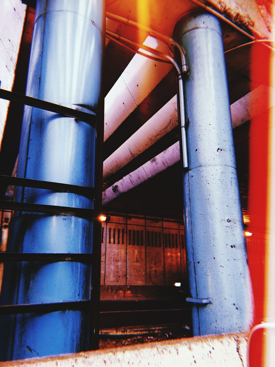 LOW ANGLE VIEW OF ILLUMINATED PIPES IN INDUSTRY