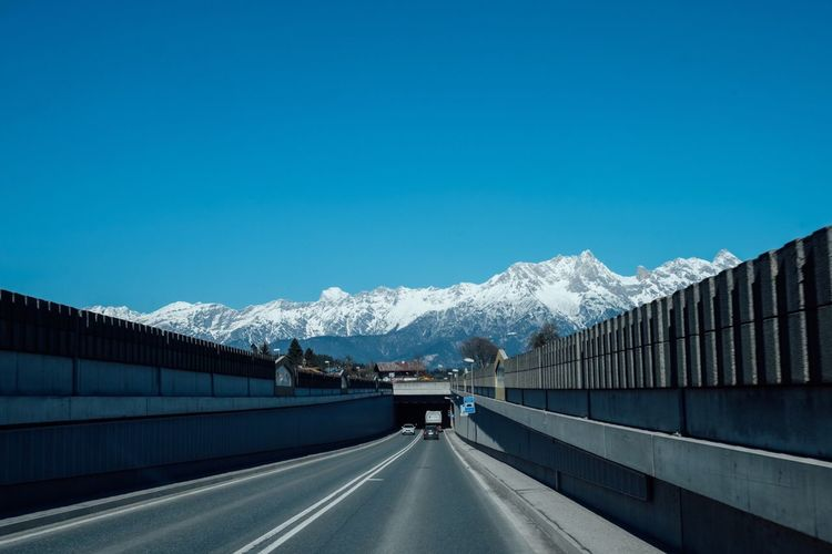 Highway leading towards snow covered mountains