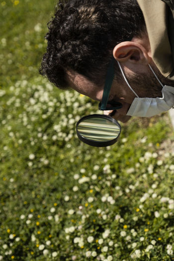 Close-up of man using magnifying glass outdoors