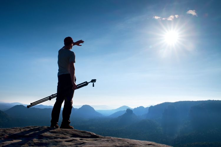 Professional photographer with tripod on cliff and think. dreamy misty sunrise in beautiful valley
