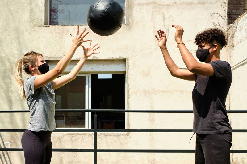 Couple wearing mask exercising with ball outdoors