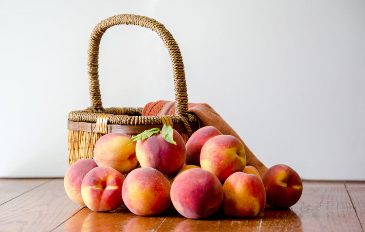 still life of peaches and a wicker basket Agriculture Basketball Fall Colors Freshness Nature Still Life Photography USA Basket Container Food Food And Drink Freshness Fruit Healthy Eating Indoors  Juicy Fruit Michigan Peaches Orange Color Organic Peanuts Peach Pile Of Peaches Still Life Table Wellbeing Yellow