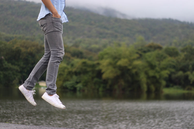 Low section of man in mid-air with hands in pockets over lake against tree mountain