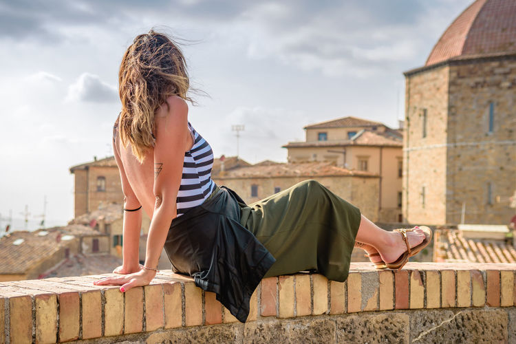 Side view of woman sitting on retaining wall