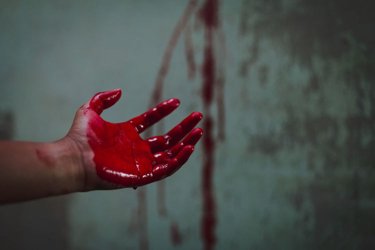 Cropped hand of person with blood against wall