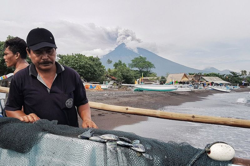 Eruption of Agung Volcano in Bali, Indonesia. The Photojournalist - 2018 EyeEm Awards Casual Clothing Cloud - Sky Day Front View Leisure Activity Lifestyles Males  Men Mid Adult Mid Adult Men Mountain Nature Outdoors People Real People Sky Water Young Adult Young Men