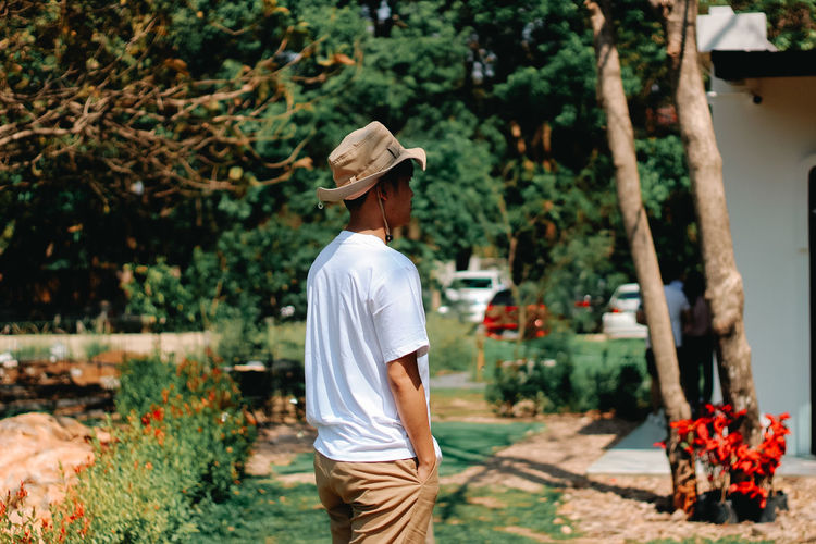 Rear view of man standing by plants