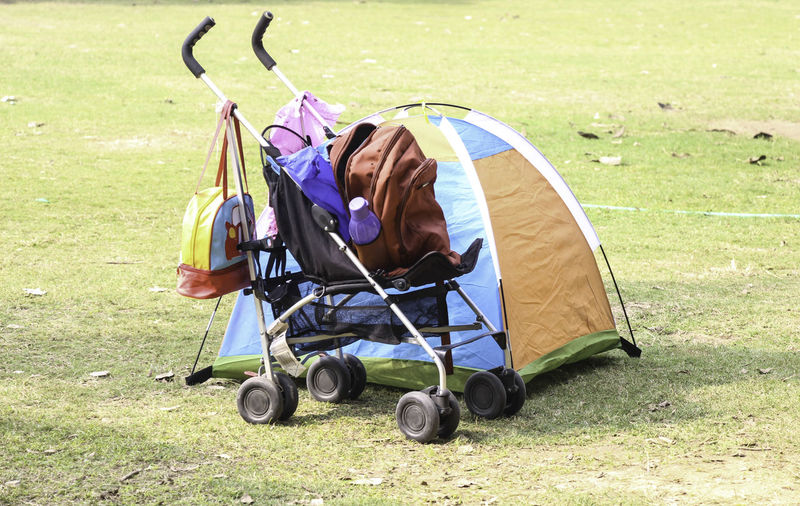 A baby stroller / carrier with some bags on it (including a purple water bottle) and a small multi colored kids tent right next to it, pitched on the grass. In the background is a garden hose pipe and some dry leaves. Baby Bag Baby Stroller Backpack Grass Outdoors Pram Small Tents Stroller Tent