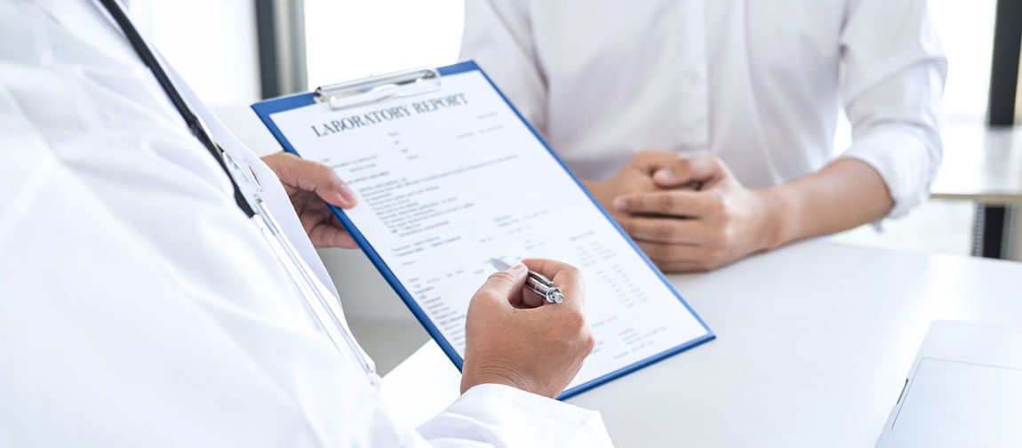 Midsection of doctor having discussion with patient