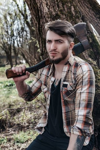 Young man holding weapon in forest