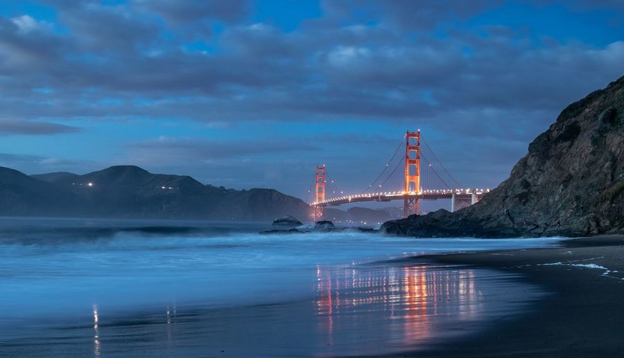 View of illuminated golden gate bridge over sea against cloudy sky at night