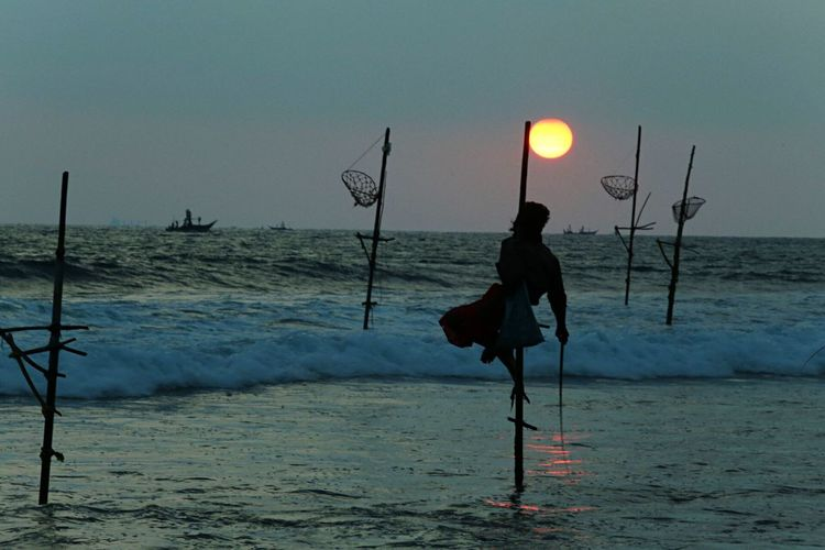 Silhouette man fishing in sea during sunset