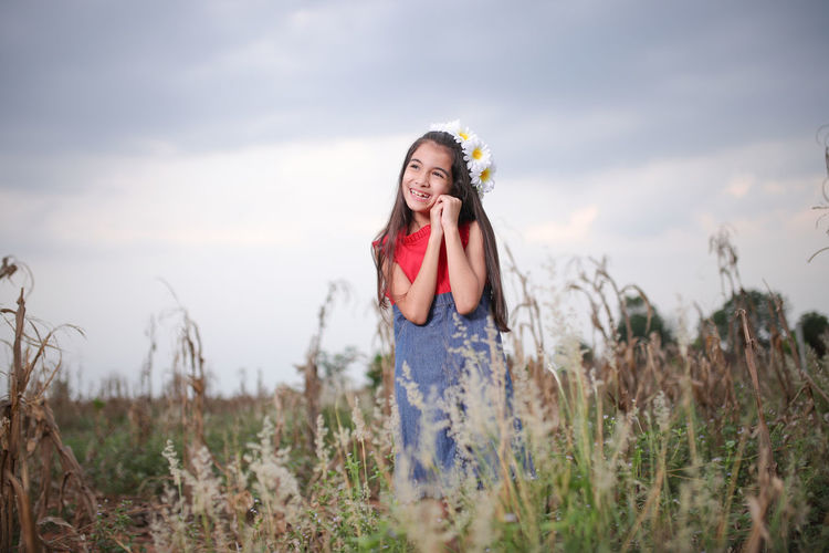 Smiling cute girl standing amidst plants on field during sunset