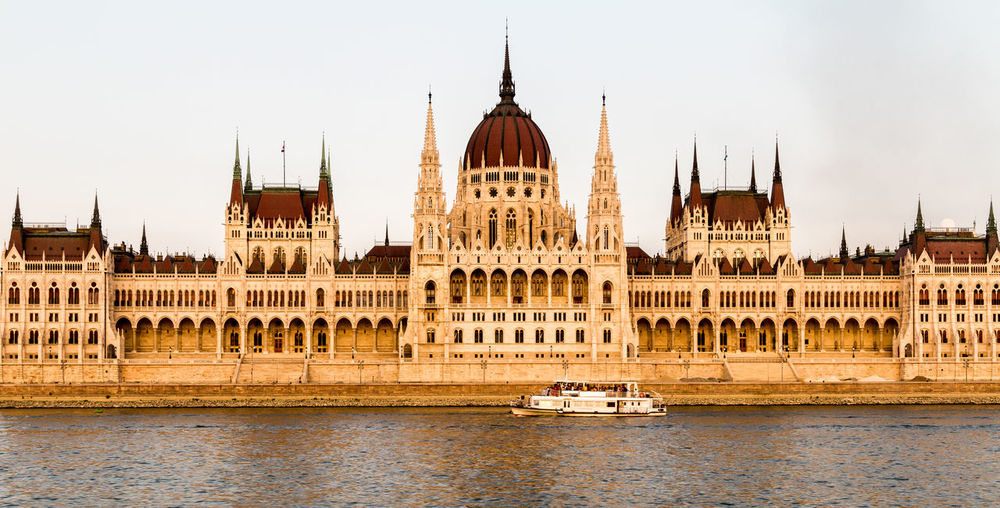 The Parliament Building in Budapest, Hungary Architecture Building Exterior Built Structure City Life Clear Sky Day Dome Façade Famous Place Government Government Building History Hungarian Parliament Building International Landmark Mode Of Transport National Landmark Outdoors Parliament Building River Spire  Tourism Transportation Travel Destinations Water Waterfront
