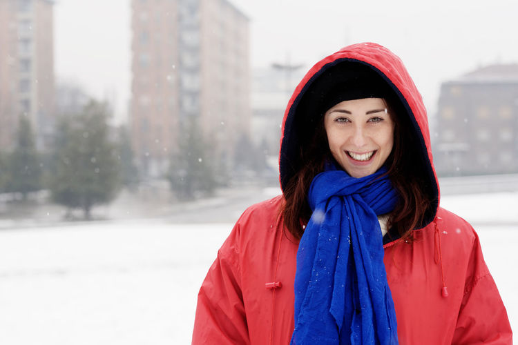 Portrait of smiling young woman at city in winter