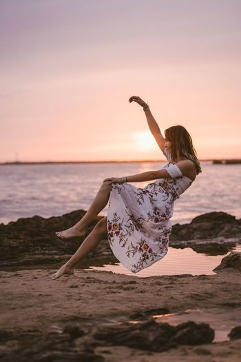 Woman Levitating At Beach Against Sky During Sunset