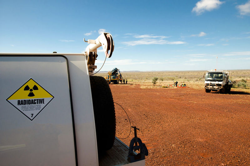 Close-up of commercial land vehicles on field against sky
