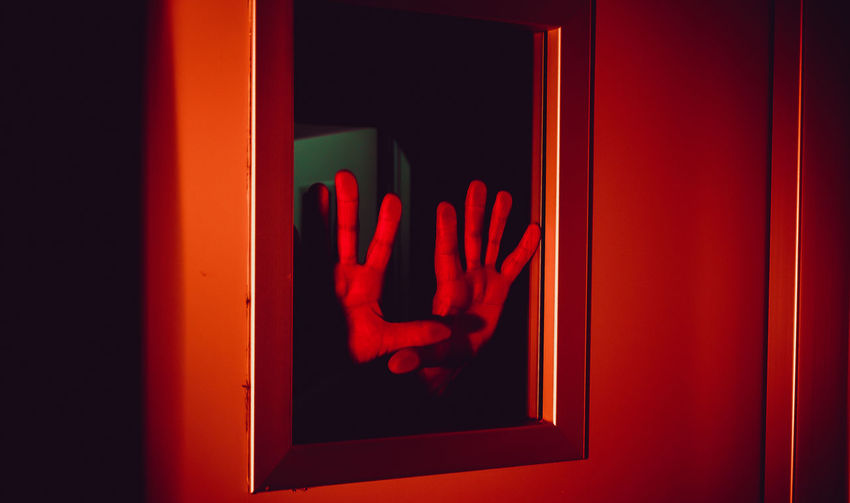 Close-up of hands pressed against window with red illumination