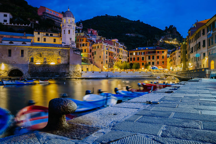 Boats in canal by illuminated buildings in city at night