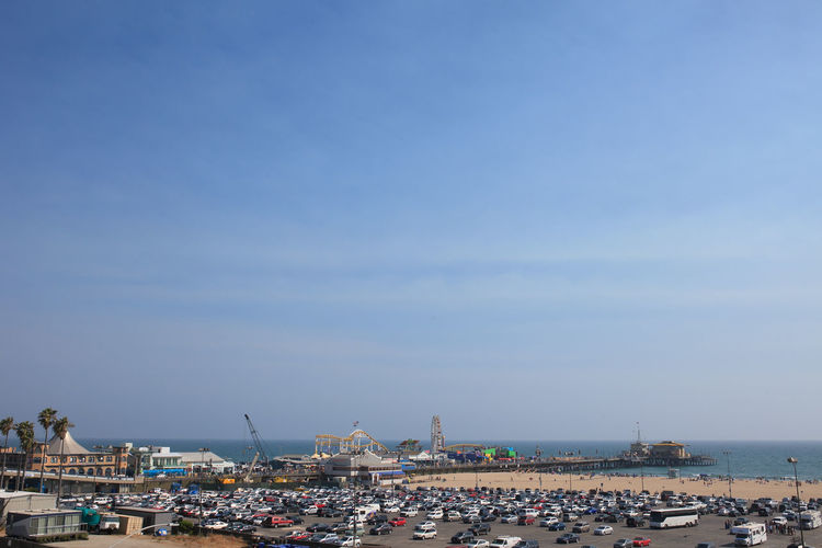 Cars In Parking Lot At Santa Monica Pier Against Blue Sky