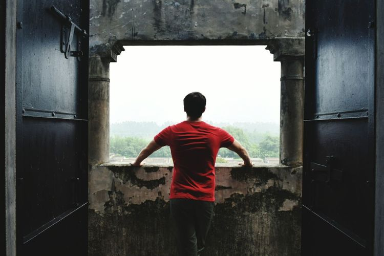 Rear view of man standing by window in old abandoned building