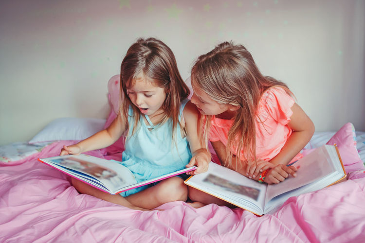 Sisters reading books while sitting on bed at home