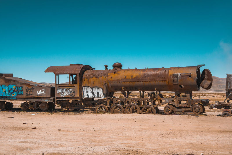Old abandoned train on field against sky