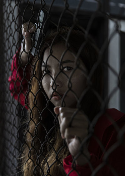 Portrait of young woman seen through chainlink fence