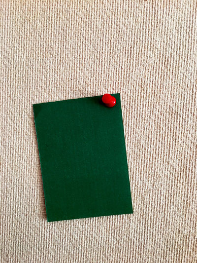 Close-up high angle view of blank green paper on textile