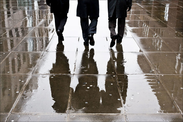 Low section of people walking on wet footpath