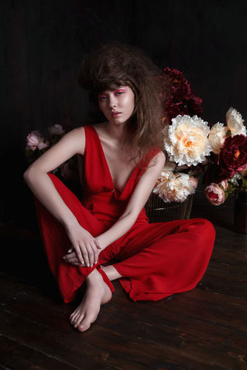 Girl in red clothes sitting among flowers Beautiful Woman Beauty Blossoms  Fashion Flower Girl With Flowers Glamour Hairstyle Looking At Camera Model One Person People Pink Make Up Portrait Real People Red Red Clothes Sitting Pose Woman In Red Young Adult Young Women