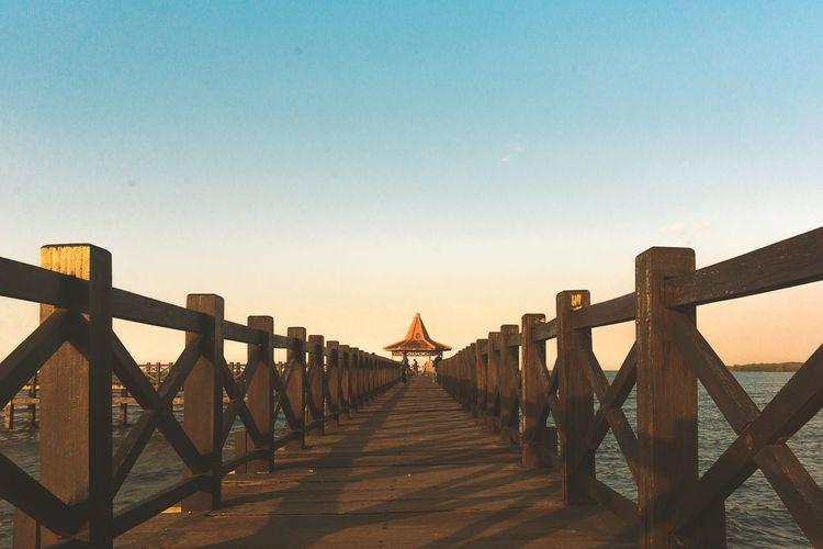 Footbridge over pier against clear sky
