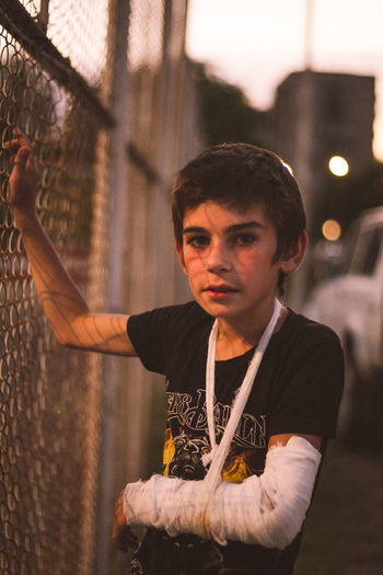 Portrait of boy with broken hand standing by fence during sunset