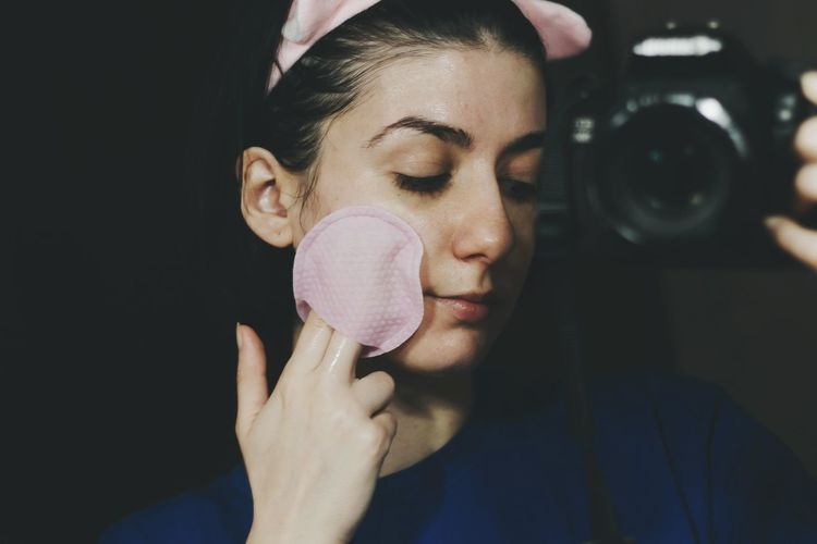 Close-up of woman applying make-up while photographing with camera at home
