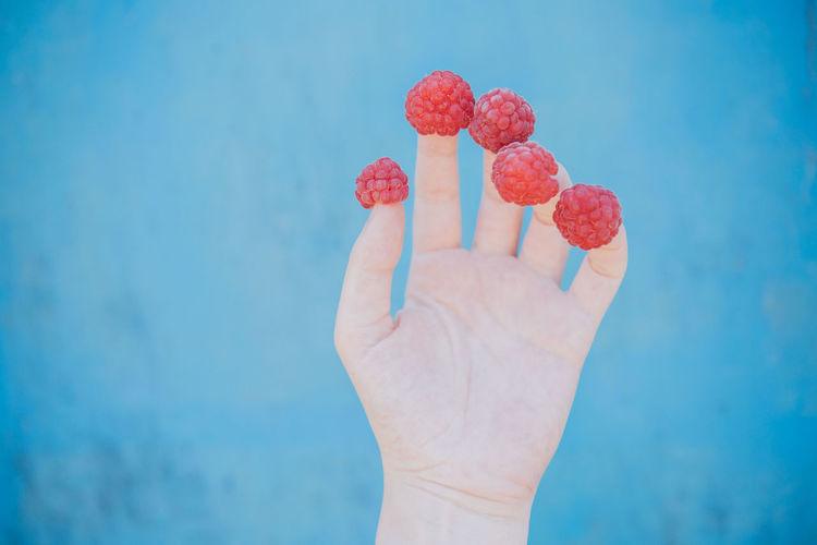 Close-up of hand holding strawberry against blue sky
