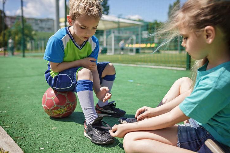 Friends sitting on soccer field